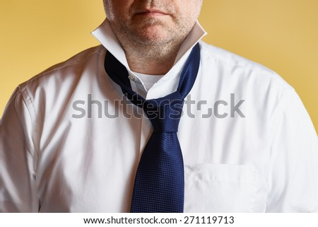 Close up, male wearing white shirt and blue tie, loose tie, yellow background