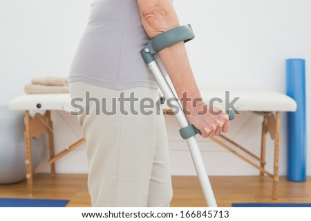 Close-up mid section of a woman with crutches standing in the hospital