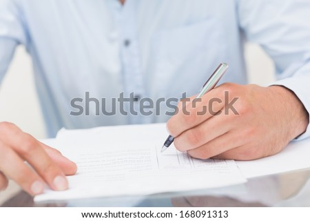Close-up mid section of a young man writing documents at the table