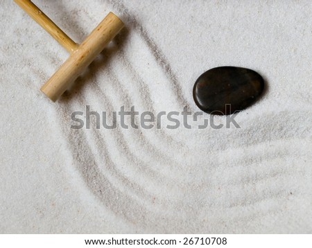 Close-up of a a Japanese zen garden with wooden rake and black stone.