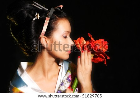 close-up of a beautiful woman holding smelling red flower