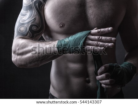 Close up of a boxer putting on straps preparing for combat on a dark background