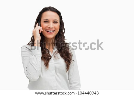 Close-up of a brunette grimacing while phoning against white background