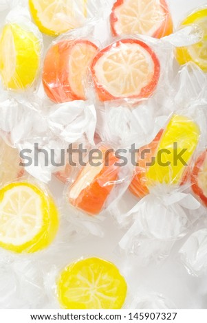 Close up of a bunch of children orange and lemon fruit sugar sweets on a white table, wrapped in see through plastic.
