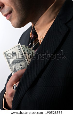 Close up of a business mans hand hiding money in his suit jacket pocket.