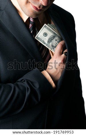 Close up of a business mans hand hiding money in his suit jacket pocket and a smirk on his face.