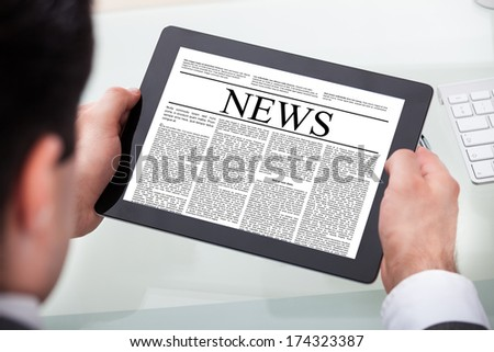Close-up Of A Businessman Reading News On Digital Tablet