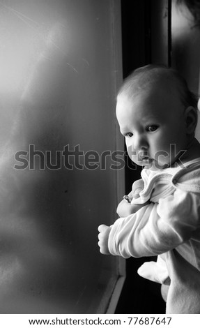 Close up of a cute baby standing next to the window