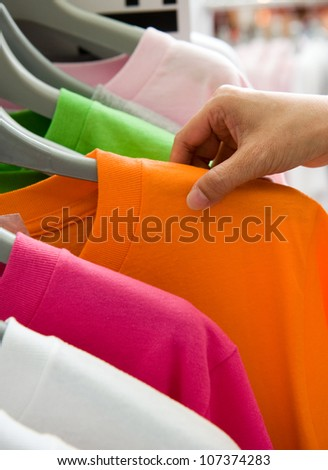 Close-up of a female customer looking for T-shirts in a fashion store ...