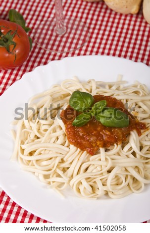 Close up of a homemade plate of pasta with tomato sauce and basil.