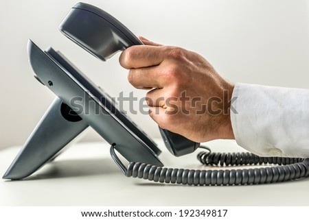 Close-up of a male hand with white sleeve shirt picking up the receiver of a black landline office telephone, with copy space on grey background. Concept of customer support.