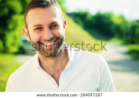 Close-up of a man smiling outside