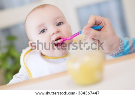 Close up of a mother feeding her baby in high chair