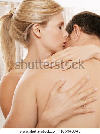 Close up of a nude couple kissing in a bedroom.