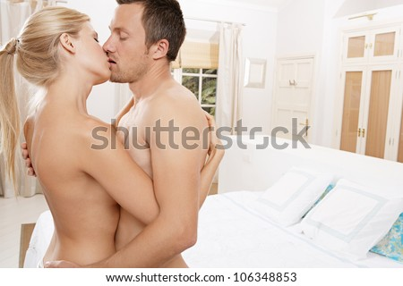 Close up of a nude couple kissing in bedroom.
