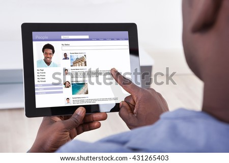 Close-up Of A Person Using Social Networking Site On Digital Tablet