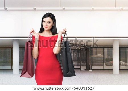 Close up of a positive woman in a bright red dress is standing with two shopping bags near a mall entrance. Concept of consumerism. 3d rendering. Mock up.