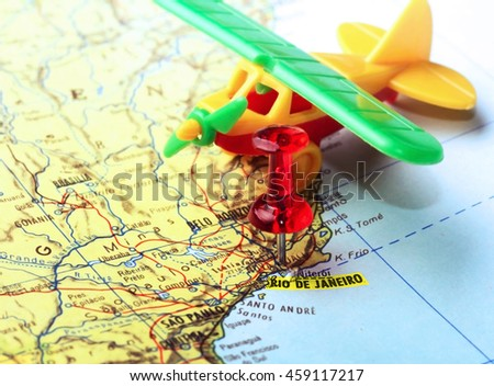 Close-up of a red pushpin on a map of  Rio de Janeiro ana airplane toy - travel concept