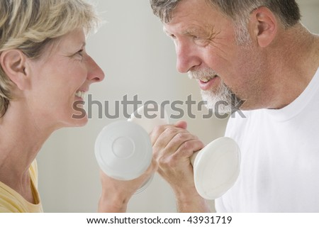 Close-up of a senior couple holding hand weights and smiling