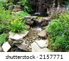 Close-up of a small stepped waterfall and pool in a landscaped oriental garden - stock photo
