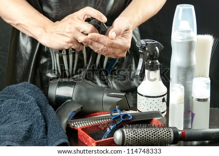 Close-up of a stylist surrounded by his tools spraying mousse into his hand.