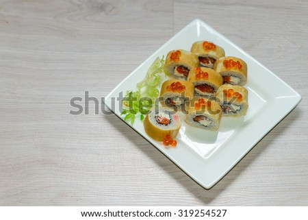 Close-up of a white plate with sushi set - Russian pancakes with caviar and strawberries , horizontal shot, shallow depth of field,  focus on near-term