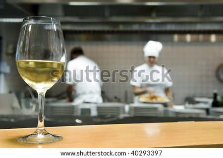 Close-up of a white wine glass with chefs on the background