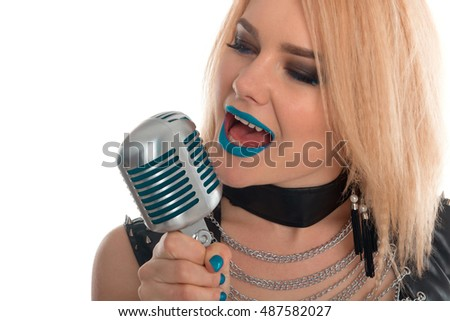 Close up of a woman with blue lips is singing to the microphone with her mouth open