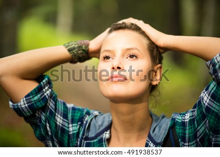 close up of a woman with men's shirt somewhere outside in nature with hands on her head