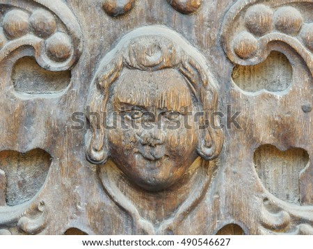 Close up of a wood carved face of an angel, ornament on an antique door . Detail of a carved wooden panel