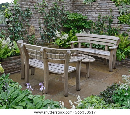 Close Up Of A Wooden Garden Seats In A Walled Garden Patio