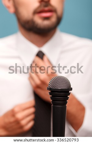 Close up of a young reporter preparing for the interview. He is standing and adjusting his tie. Focus on the microphone near the man