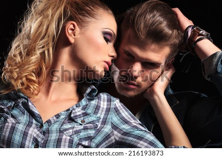 Close up of a young sexy woman looking away while hugging her lover, against studio background