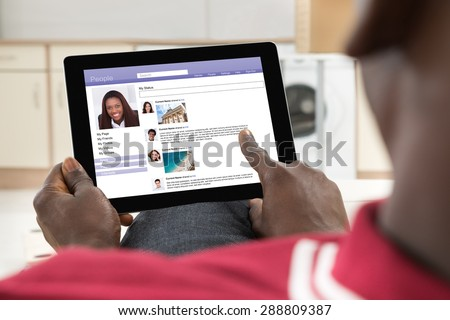 Close-up Of African Young Man Chatting On Social Networking Site Using Digital Tablet