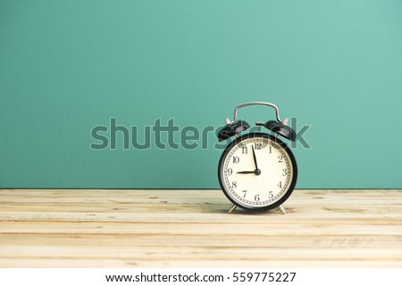 Close up of alar clock on the wooden table over blue background