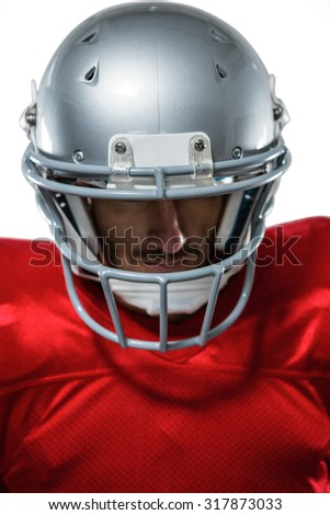 Close-up of American football player in red jersey looking down against white background