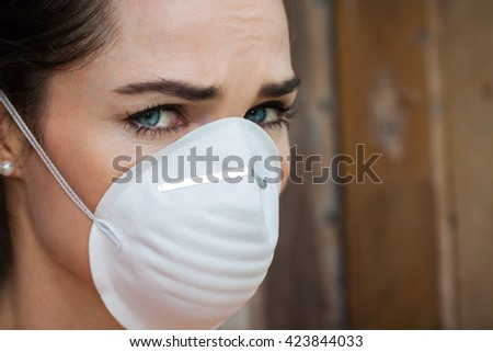 Close-up of an unhappy woman wearing a face mask to deal with virus or pollution.