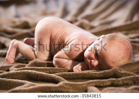 Close-up of bare 9 day old newborn baby lying on blanket