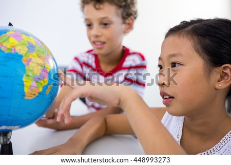 Close-up of boy and girl looking at globe in classroom