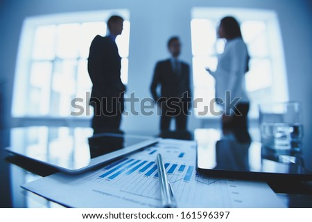 Close-up of business document and touchpads at workplace on background of office workers interacting