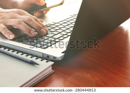 Close up of business man hand working on laptop computer on wooden desk as concept