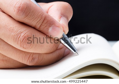 Close up of business man hand writing diary