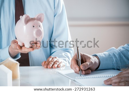Close Up of Business Man Holding Pink Piggy Bank in Meeting with Co-Worker Taking Notes in Note Book, Real Estate or Investment Concept Image