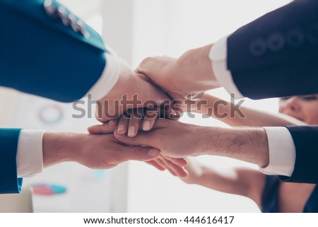 Close-up of business team in formalwear putting their hands on top of each other