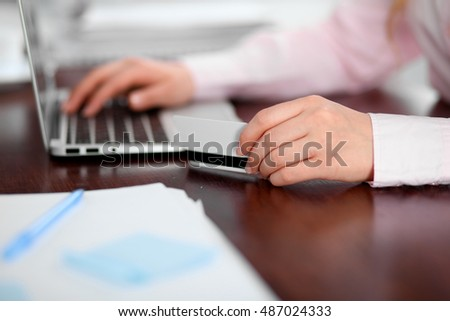Close up of business woman hands using credit card and laptop computer