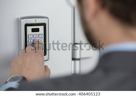 Close up of businessman hand entering security system code