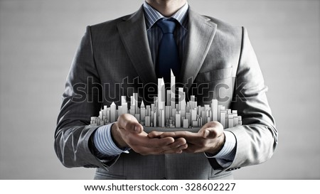 Close up of businessman hand holding construction model