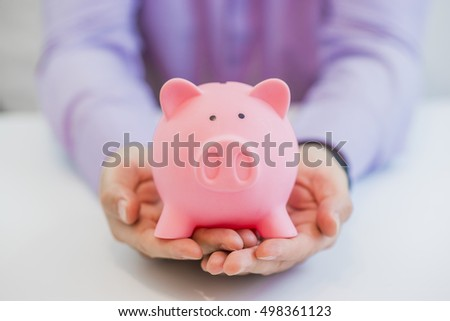 Close-up Of Businessman's Hand Holding Piggybank Over White Background
