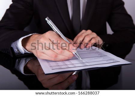 Close-up Of Businessman Writing On Paper With Pen