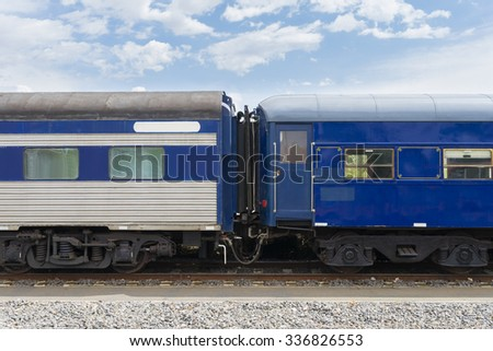 Close-up of carriages of blue, vintage passenger train in railroad